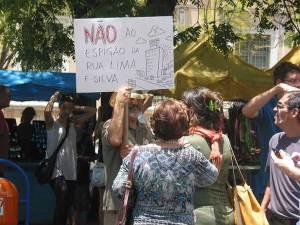 Cidadãos demonstravam sua inconformidade. Cartunista Santiago e seu cartaz contra os espigões em seu bairro.