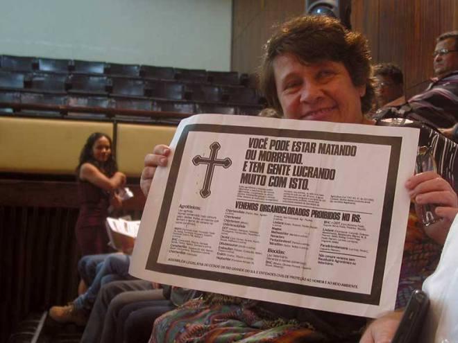 Lívia, filha da pioneira ambientalista Hilda Zimmermann, mostra um cartaz sobre a lei aprovada nos anos 80.